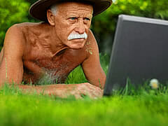 shirtless white-haired man in grass on computer
